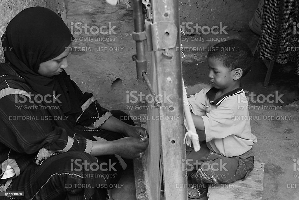Moroccan mother and son weaving on either side of loom royalty-free stock photo