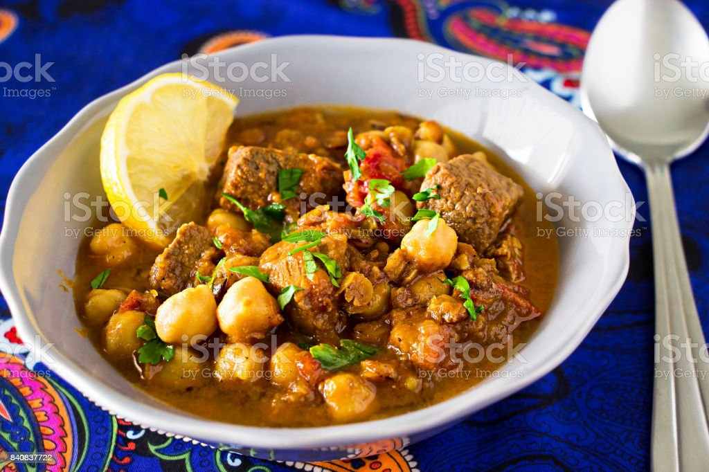 Moroccan soup harira with Meat Chickpeas Lentil Tomato Lemon and Spices in gray bowl. Arabic pattern background. stock photo