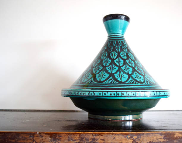 Moroccan tagine isolated Green and black Moroccan tagine (cooking vessel) on a table el tajin stock pictures, royalty-free photos & images