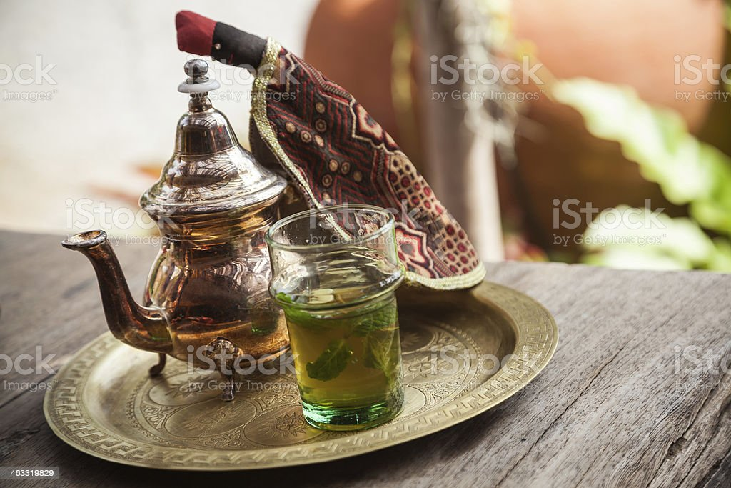 Moroccan tea pot next to glass of mint tea on bronze plate  stock photo