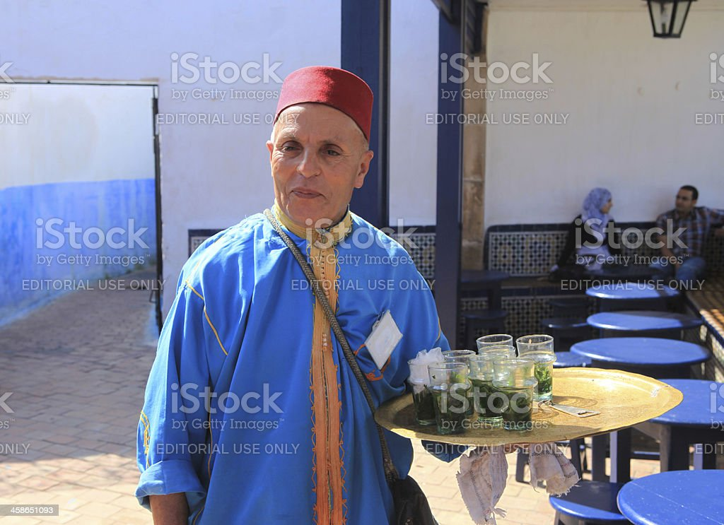 Moroccan waiter serving mint tea in a restaurant, Rabat, Morocco royalty-free stock photo