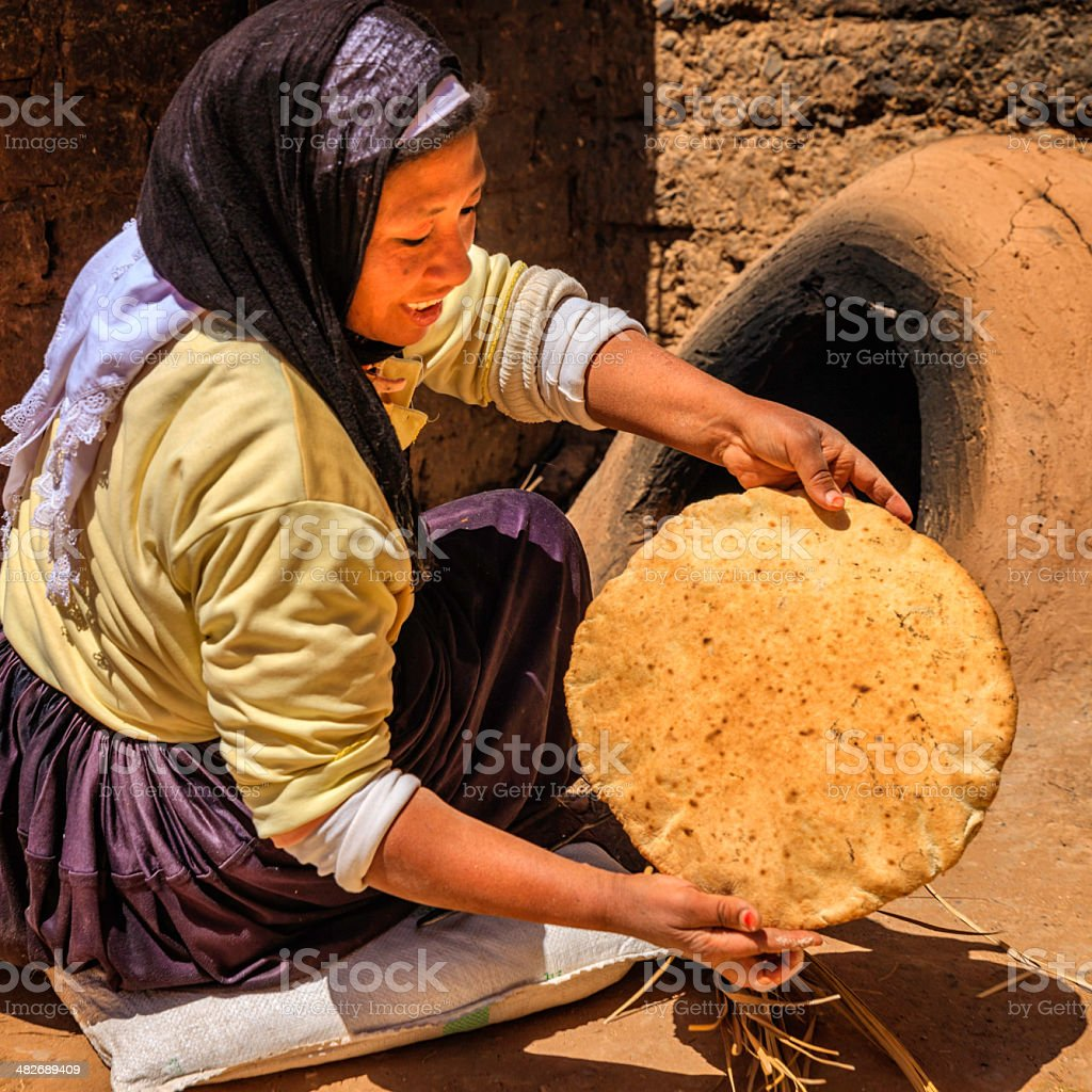 Moroccan woman baking bread - khubz stock photo