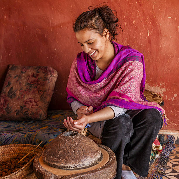 Moroccan woman producing argan oil by traditional methods stok fotoğrafı