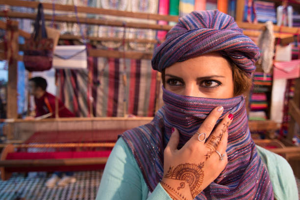 Moroccan woman with silk scarf covering her face in Morocco with looms in the background stock photo
