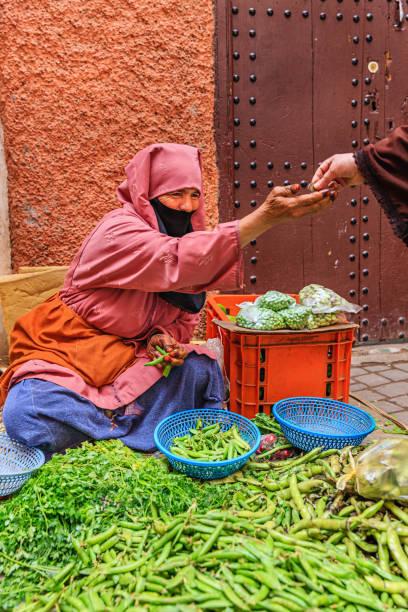Morrocan woman selling vegetables on street market, Marrakech – zdjęcie