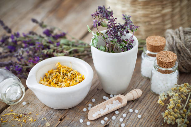 Mortar and bowl of dried healing herbs and bottles of homeopathic globules.  Homeopathy medicine concept. stock photo