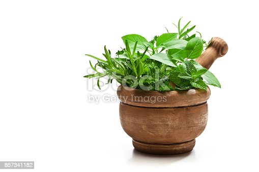 Front view of an old wooden mortar filled with fresh organic herbs for cooking shot on white background. The mortar is at the right of an horizontal frame leaving useful copy space for text and/or logo at the left. Predominant colors are white, brown and green. DSRL studio photo taken with Canon EOS 5D Mk II and Canon EF 100mm f/2.8L Macro IS USM