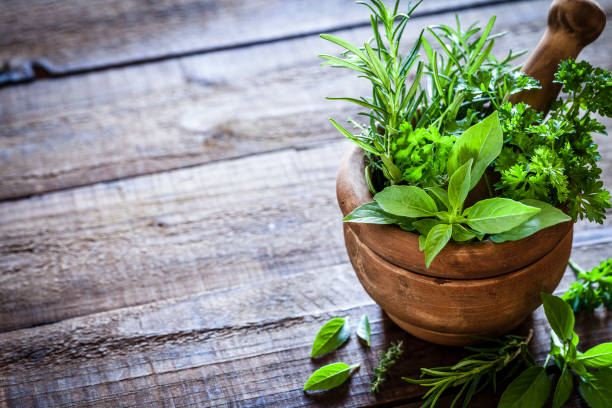 mortar and pastle with fresh herbs for cooking on rustic wooden table - naturopathy stock photos and pictures