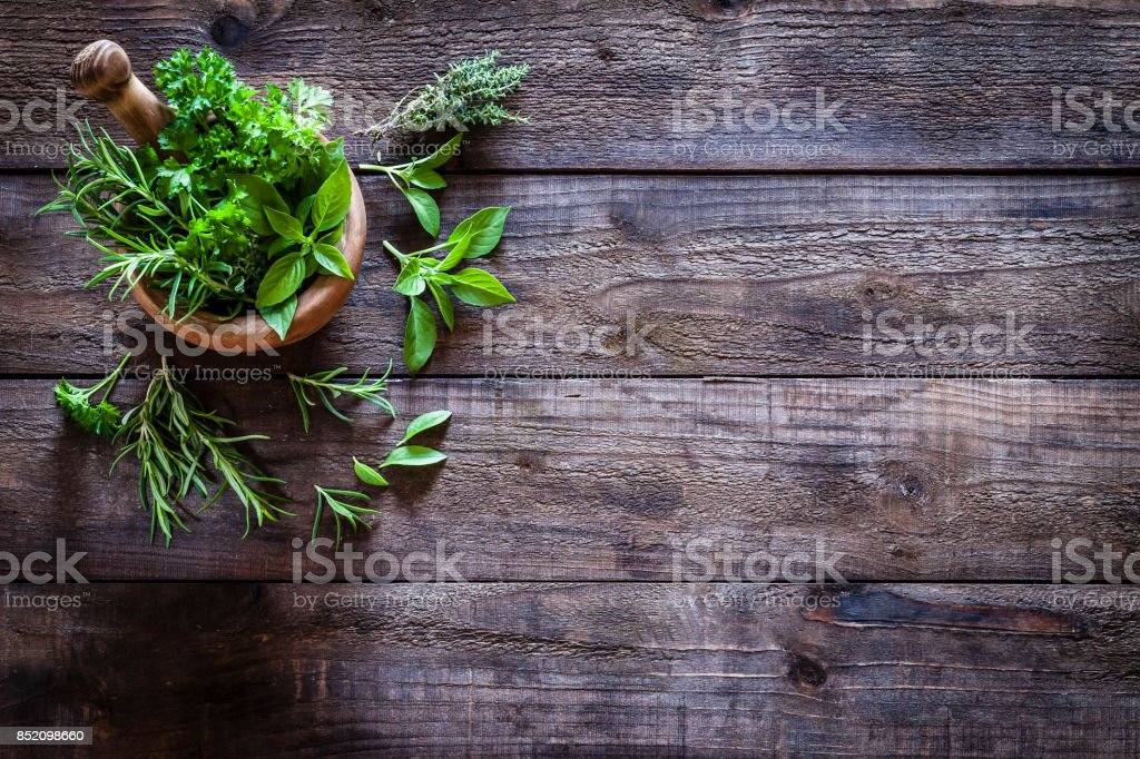 Mortar and pastle with fresh herbs for cooking on rustic wooden table stock photo