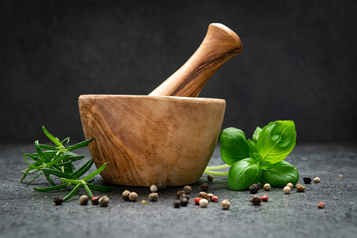Mortar and pastle with fresh herbs on Dark background