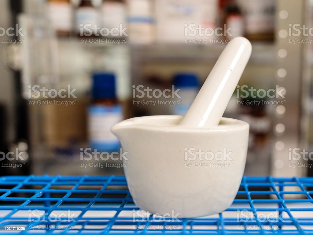 A mortar and pestle in a pharmacy with medications in the background