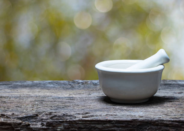 mortar and pestle on wood table stock photo