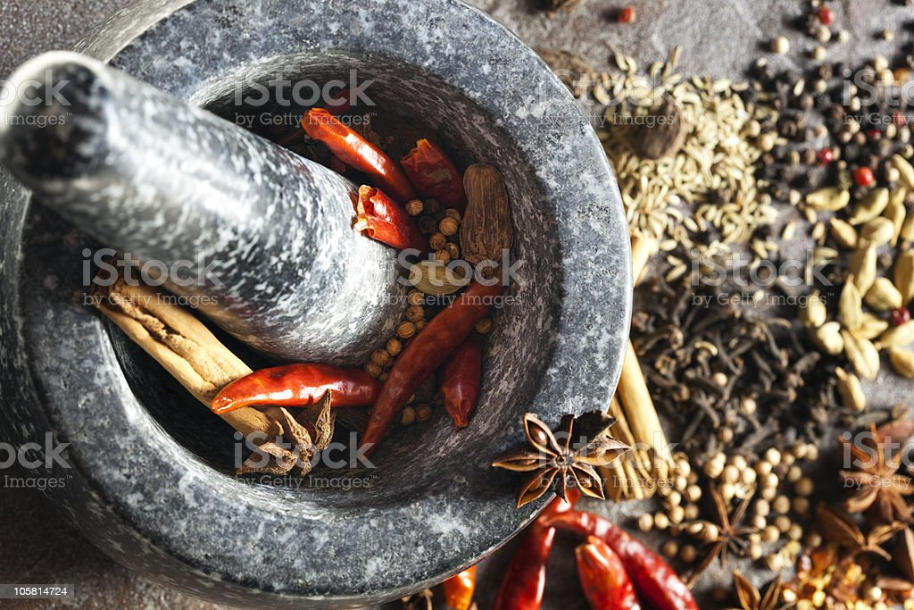 Mortar and pestle surrounded by various spices stock photo