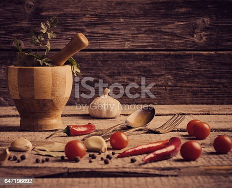 istock Mortar and pestle with pepper and spices on wooden table 647196692