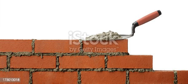 A trowel with mortar sitting on a brick wall.Please see some similar pictures from my portfolio: