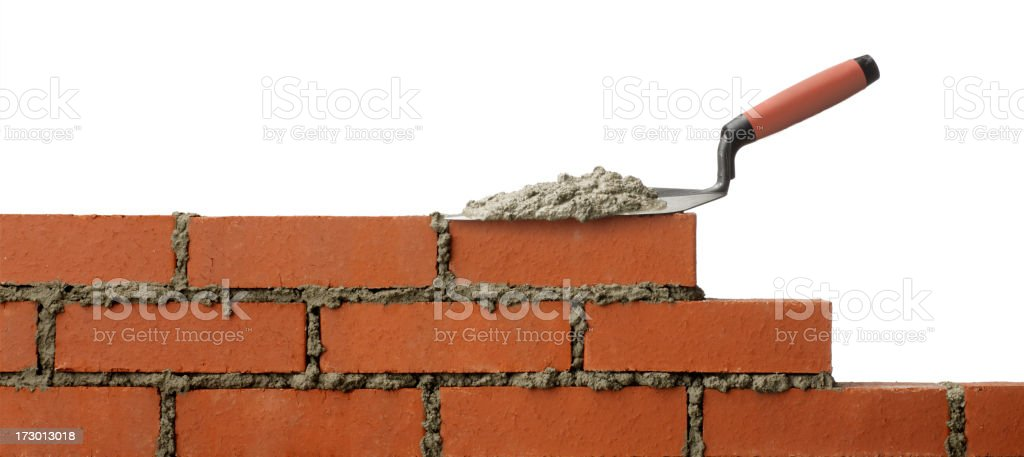 Mortar on trowel sitting on unfinished brick wall stock photo