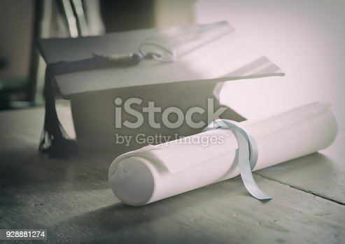 istock Mortarboard and graduation scroll tied with blue ribbon. 928881274