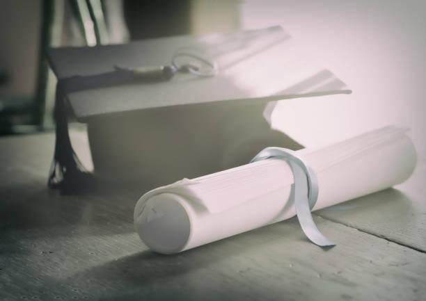 Doktorhut und Graduierung Scroll mit blauem Band gebunden. – Foto