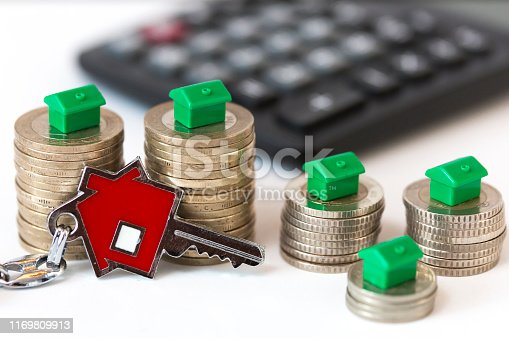Mortgage and real estate concept. Model houses, coins, red house shaped keychain and calculator. Accumulate to become homeowners and family budget. Horizontal close up detail on white background.