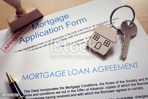 Mortgage loan agreement application with  key on house shaped keyring