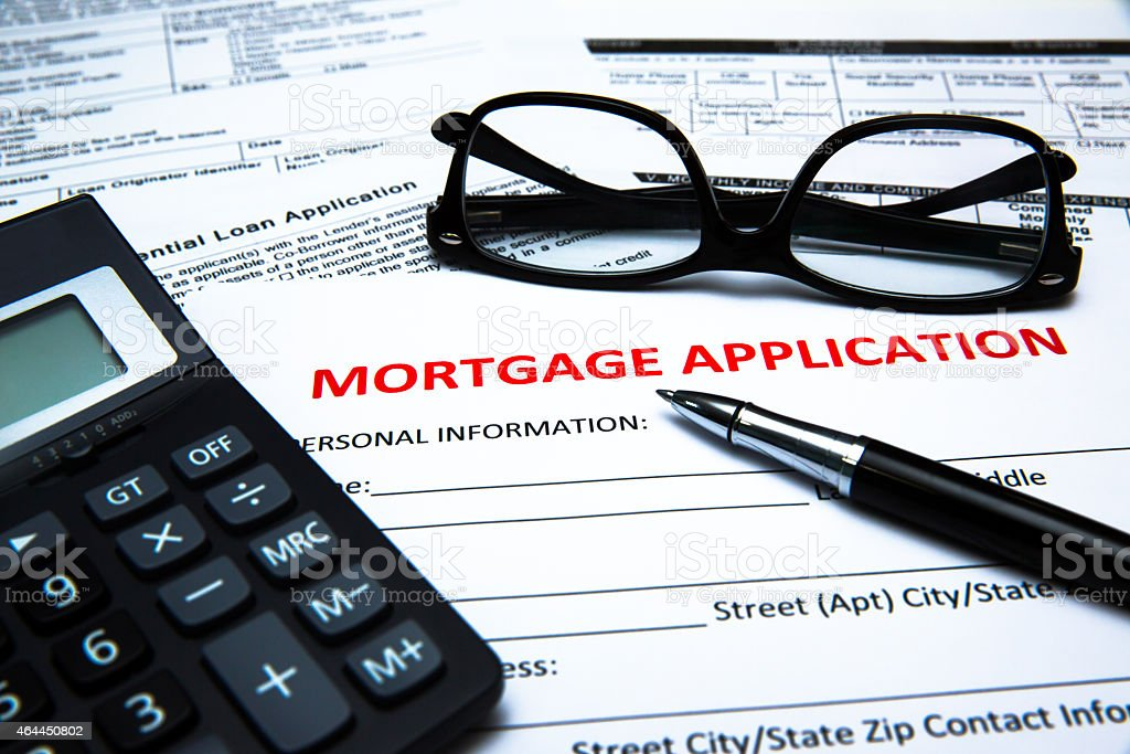 A mortgage application on a desk with a calculator and pen stock photo