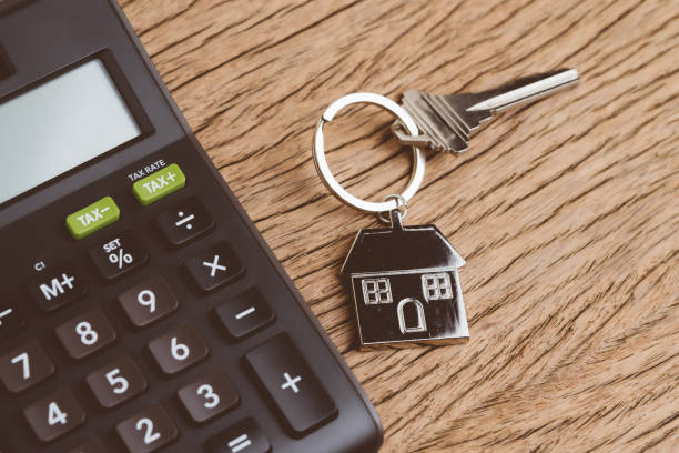 mortgage calculation or buy and sell house, property and real estate, home key with house keyring or keychain with black calculator on wooden table - white background стоковые фото и изображения