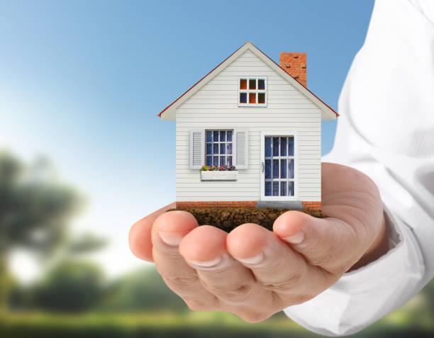 hypotheken sie-konzept von haus in der hand - hausmodell stock-fotos und bilder