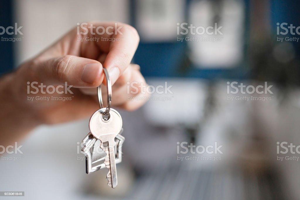 Hypothek-Konzept. Männer Hand Taste mit Haus förmigen Schlüsselbund. Moderne helle Lobby Interieur. Immobilien, Umzug oder Vermietung von Immobilien. – Foto