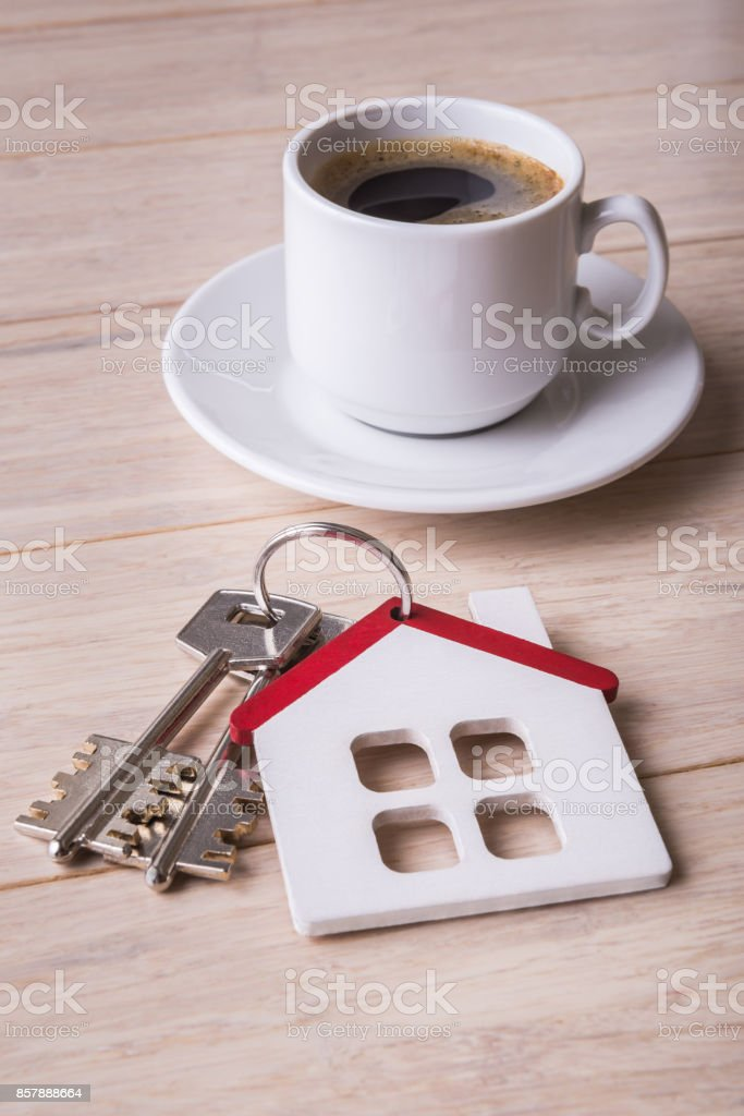 Mortgage concept with house model and coffee cup stock photo