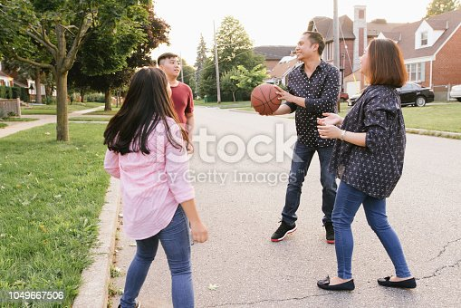 Parents and teens playing basketball together