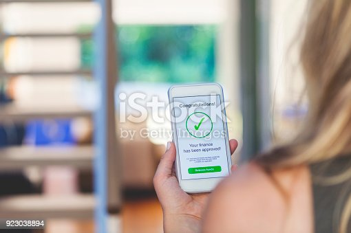 923038914istockphoto Mortgage Loan approval on mobile phone in a house. 923038894