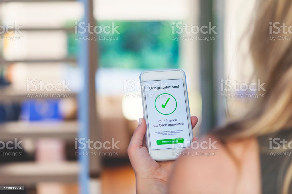 Mortgage Loan approval on mobile phone in a house. stock photo