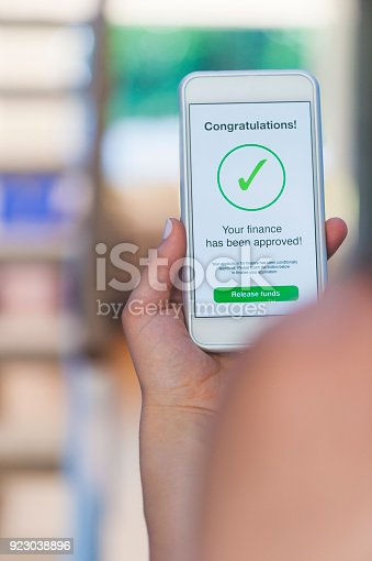 923038914istockphoto Mortgage Loan approval on mobile phone in a house. 923038896