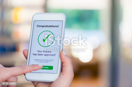 923038914istockphoto Mortgage Loan approval on mobile phone in a house. 923038902