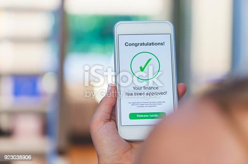 923038914istockphoto Mortgage Loan approval on mobile phone in a house. 923038906