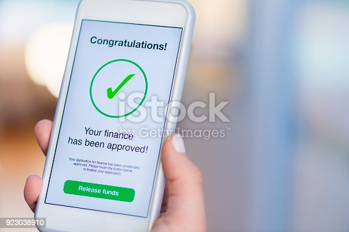 923038914istockphoto Mortgage Loan approval on mobile phone in a house. 923038910