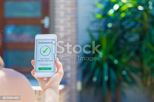 923038914istockphoto Mortgage Loan approval on mobile phone in front of house. 922094452