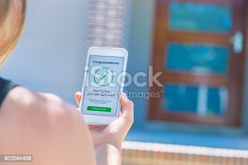 923038914istockphoto Mortgage Loan approval on mobile phone in front of house. 922094458