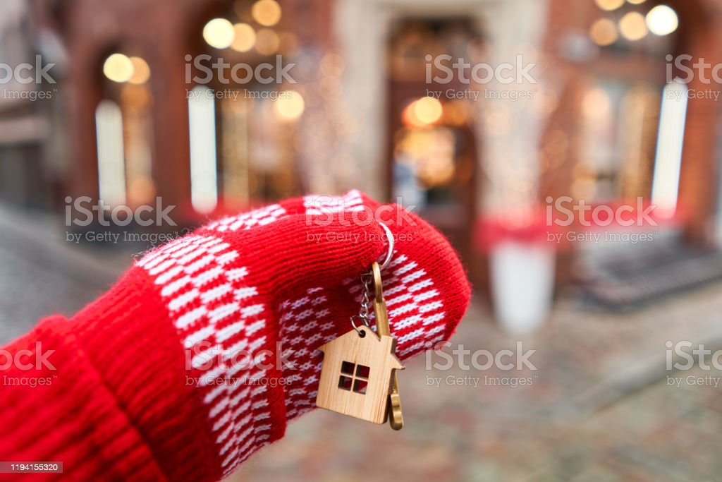 Mortgage or rent concept. Hand in red mitten holding key with house shaped keychain. Real estate, hypothec, moving home or renting property. Christmas mood in blurred background. Mortgage or rent concept. Hand in red mitten holding key with house shaped keychain. Real estate, hypothec, moving home or renting property. Christmas mood in blurred background Adult Stock Photo