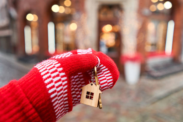 Mortgage or rent concept. Hand in red mitten holding key with house shaped keychain. Real estate, hypothec, moving home or renting property. Christmas mood in blurred background. stock photo