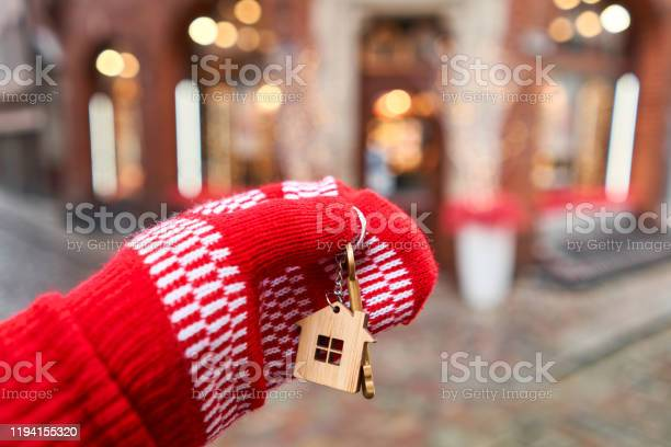 Mortgage Or Rent Concept Hand In Red Mitten Holding Key With House Shaped Keychain Real Estate Hypothec Moving Home Or Renting Property Christmas Mood In Blurred Background Stock Photo - Download Image Now