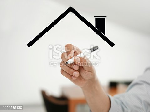 businessman drawing a symbolic town house on a virtual board