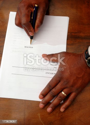 Close up. Hands signing a mortgage application.