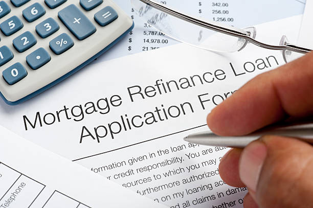 mortgage refinance application form with pen, calculator, writin - mortgages and loans stock pictures, royalty-free photos & images