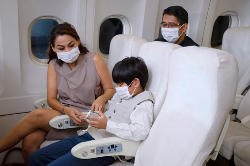 Morther is fasten seat belt for the son. They are on the plane and wearing protective face mask. Security and safety concept.