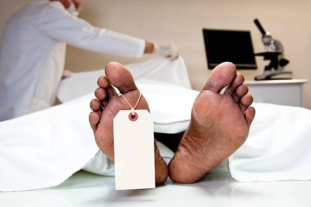Médico Legista Mortician, cobrindo dead body em morgue. Pés, etiqueta para o dedão. - foto de acervo