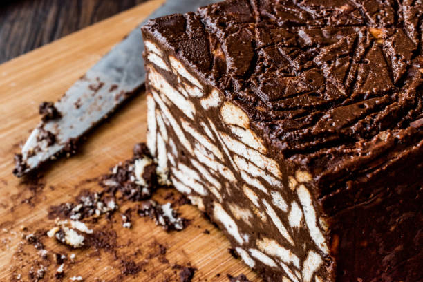 Mosaico de Chocolate e bolo de Biscuit com faca na superfície de madeira. - foto de acervo