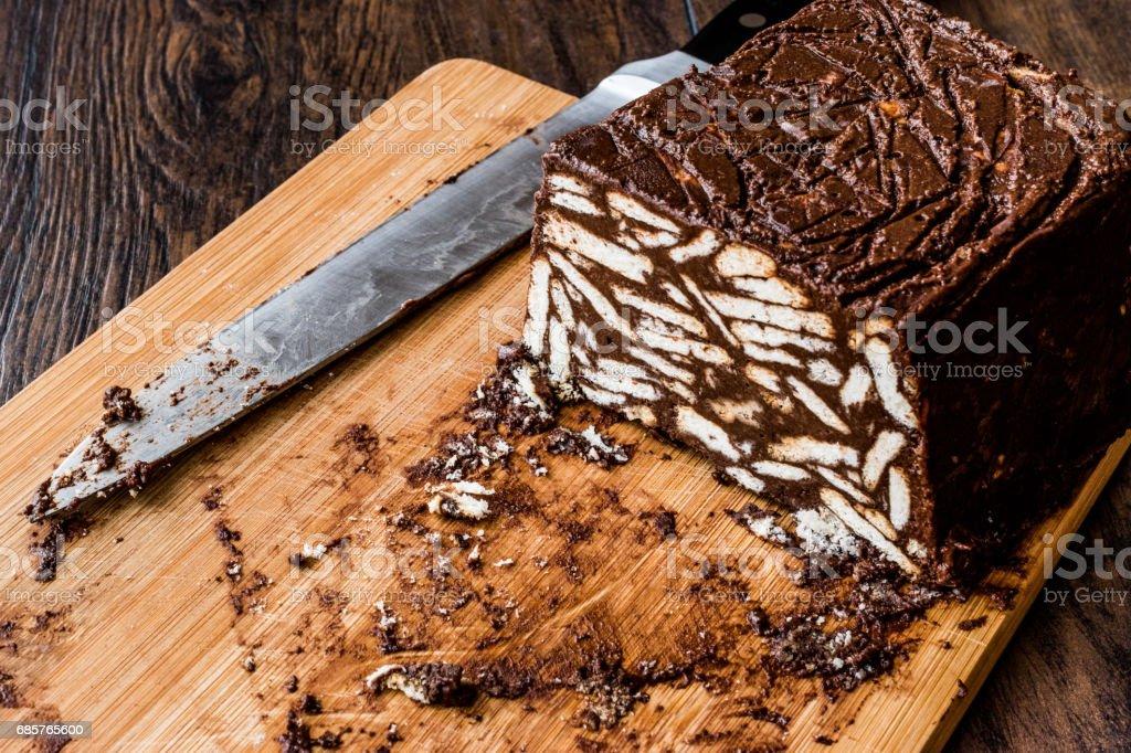 Mosaic choklad och kex kaka med kniv på träytan. royaltyfri bildbanksbilder