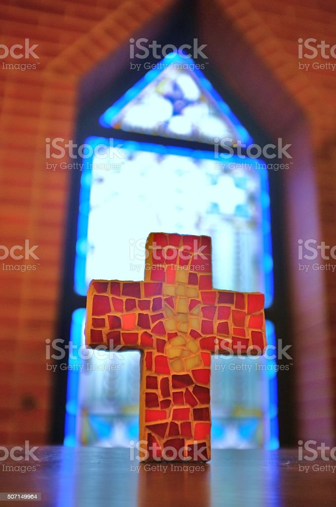 Mosaic cross shape in front of stained glass church window stock photo