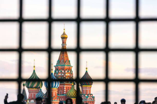 Moscow behind bars, Russia. St. Basil's Cathedral on Red Square with a large number of people is hidden behind bars. sanctions stock pictures, royalty-free photos & images